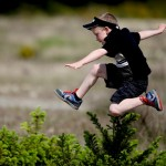 child jumping over hedge