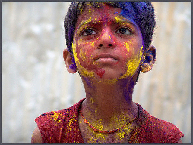 child with face painted looking serious